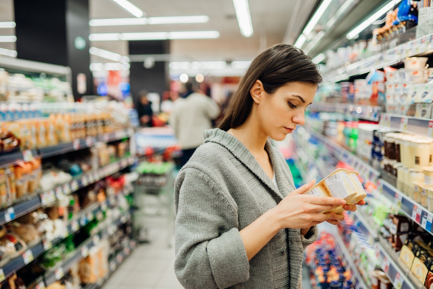 Low FODMAP diet: A woman reads the ingredients on a package of yogurt