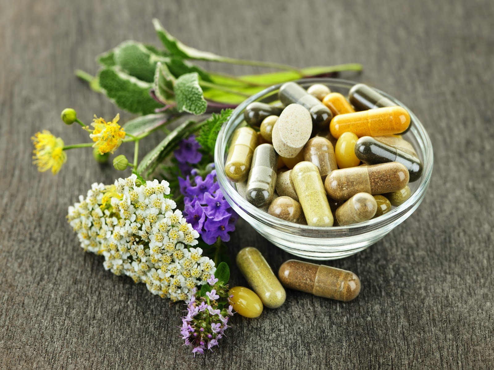 Thyroid supplements in a bowl, surrounded by herbal remedies