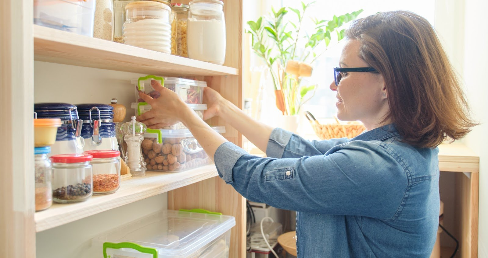 woman taking kitchenware and food from the shelves