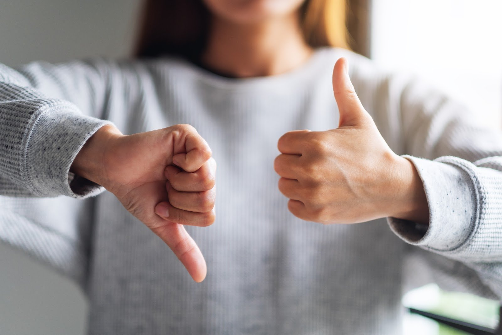 Soil-based probiotics: Woman making thumbs up and thumbs down hands sign