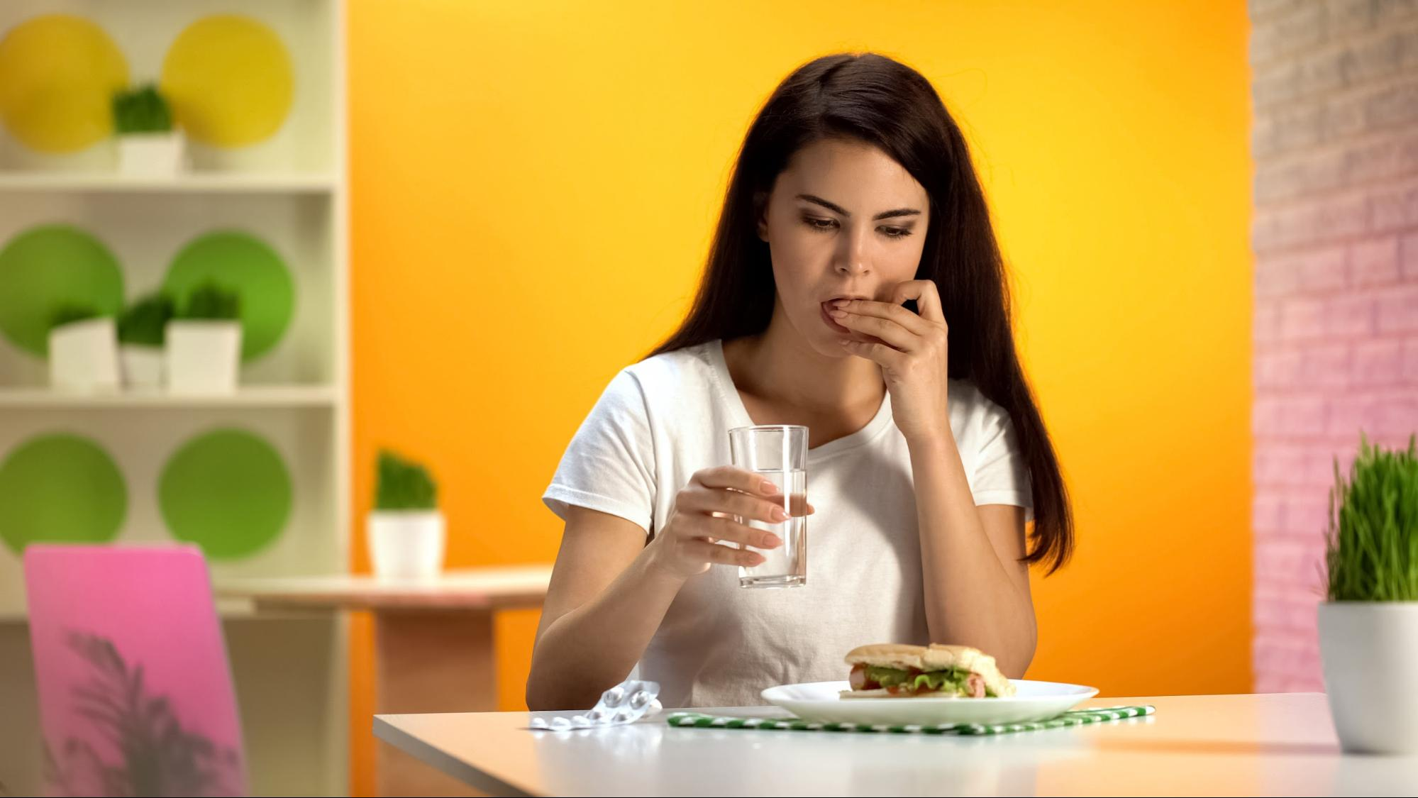 A woman taking a pill while eating