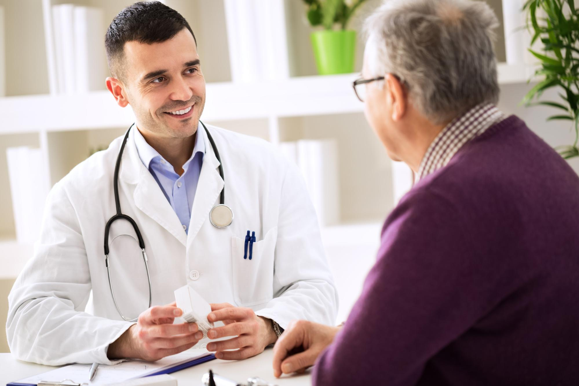 Betaine HCl: A smiling doctor talking to an old male patient