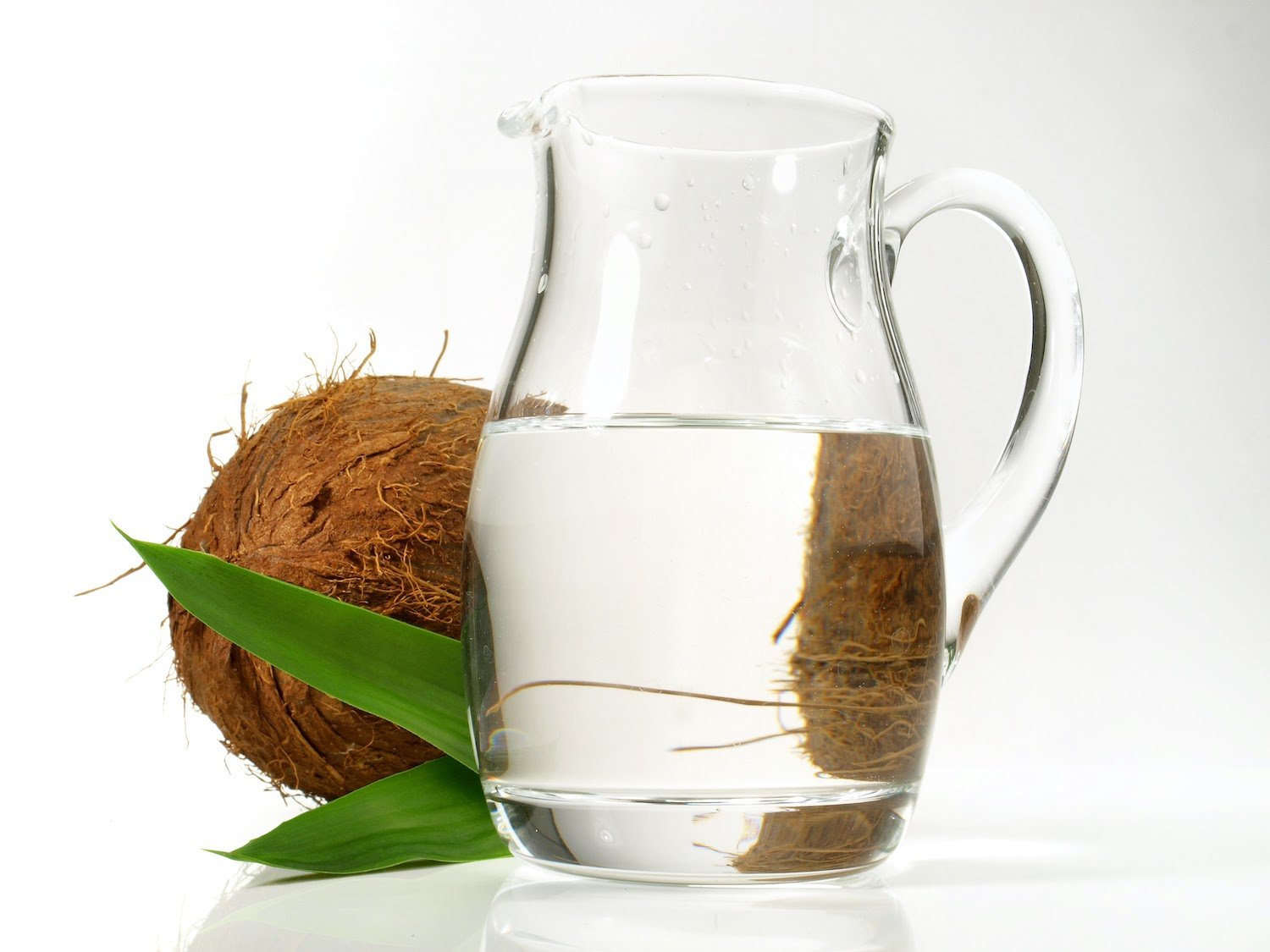 MCT oil vs coconut oil: A pitcher of coconut oil with a coconut in the background