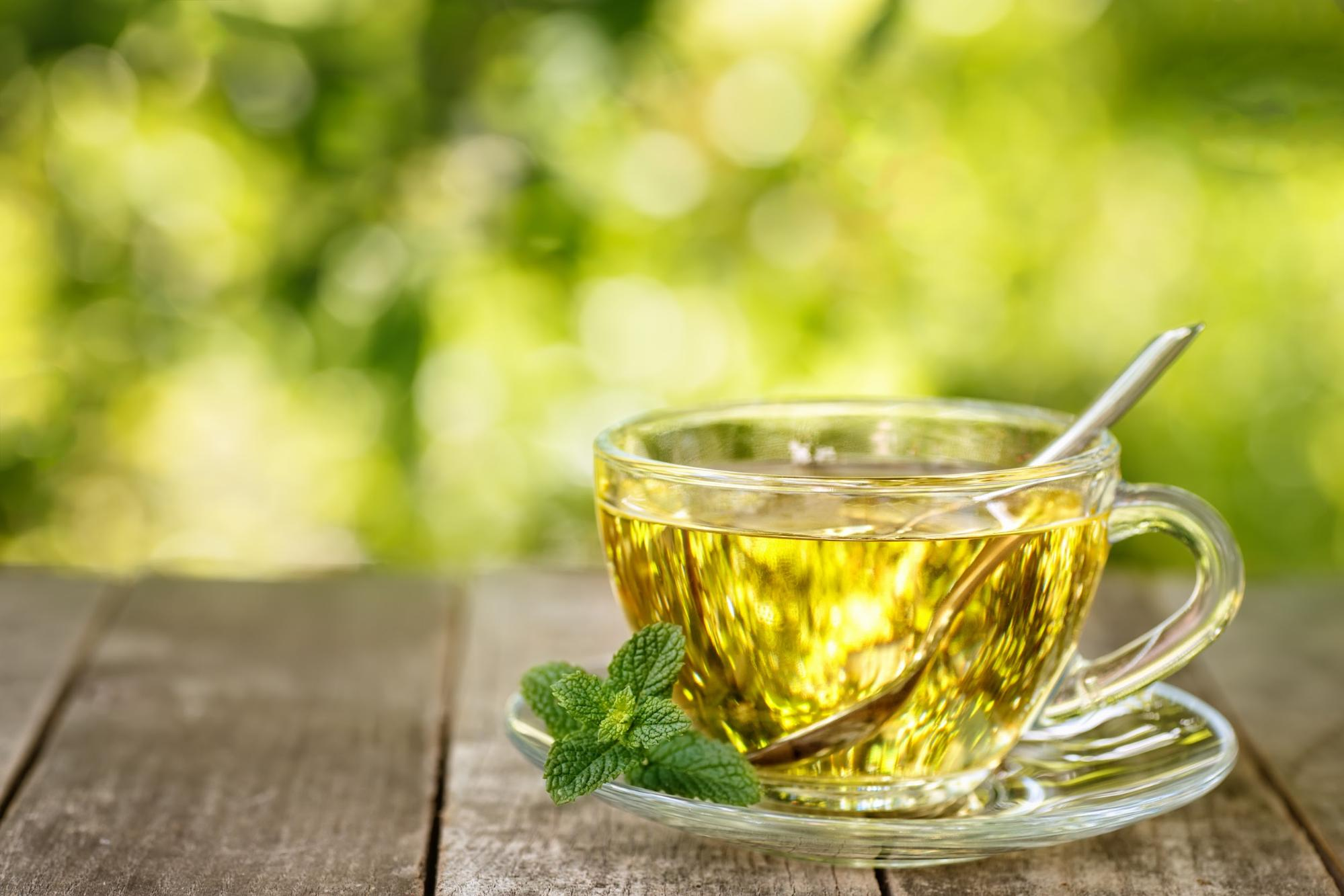 Mint tea on a glass teacup & saucer with mint leaves