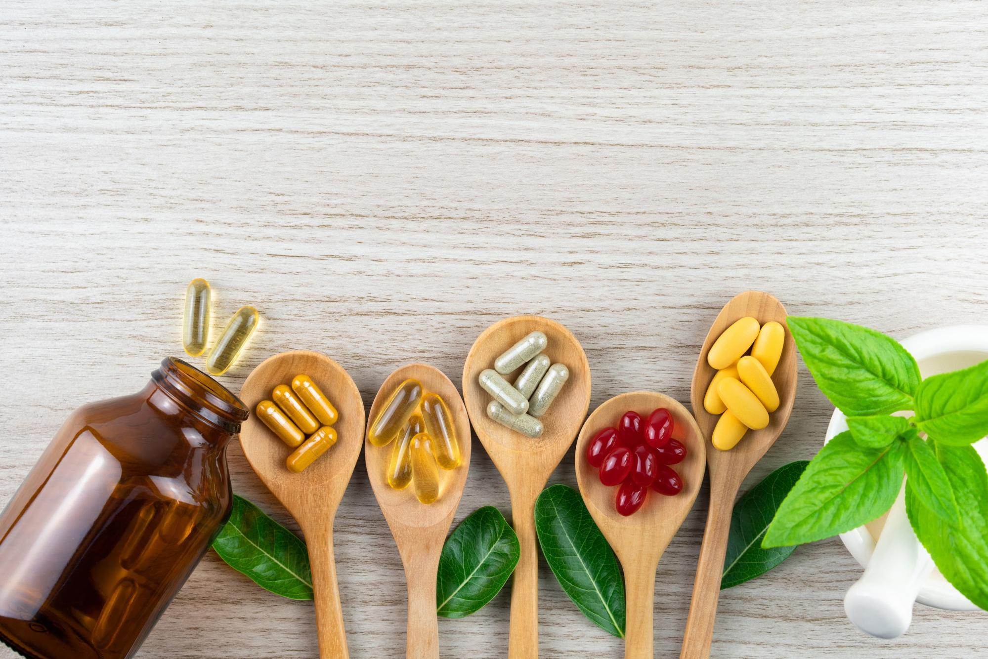 Supplements for PCOS: Variety of vitamins and minerals on wooden spoons