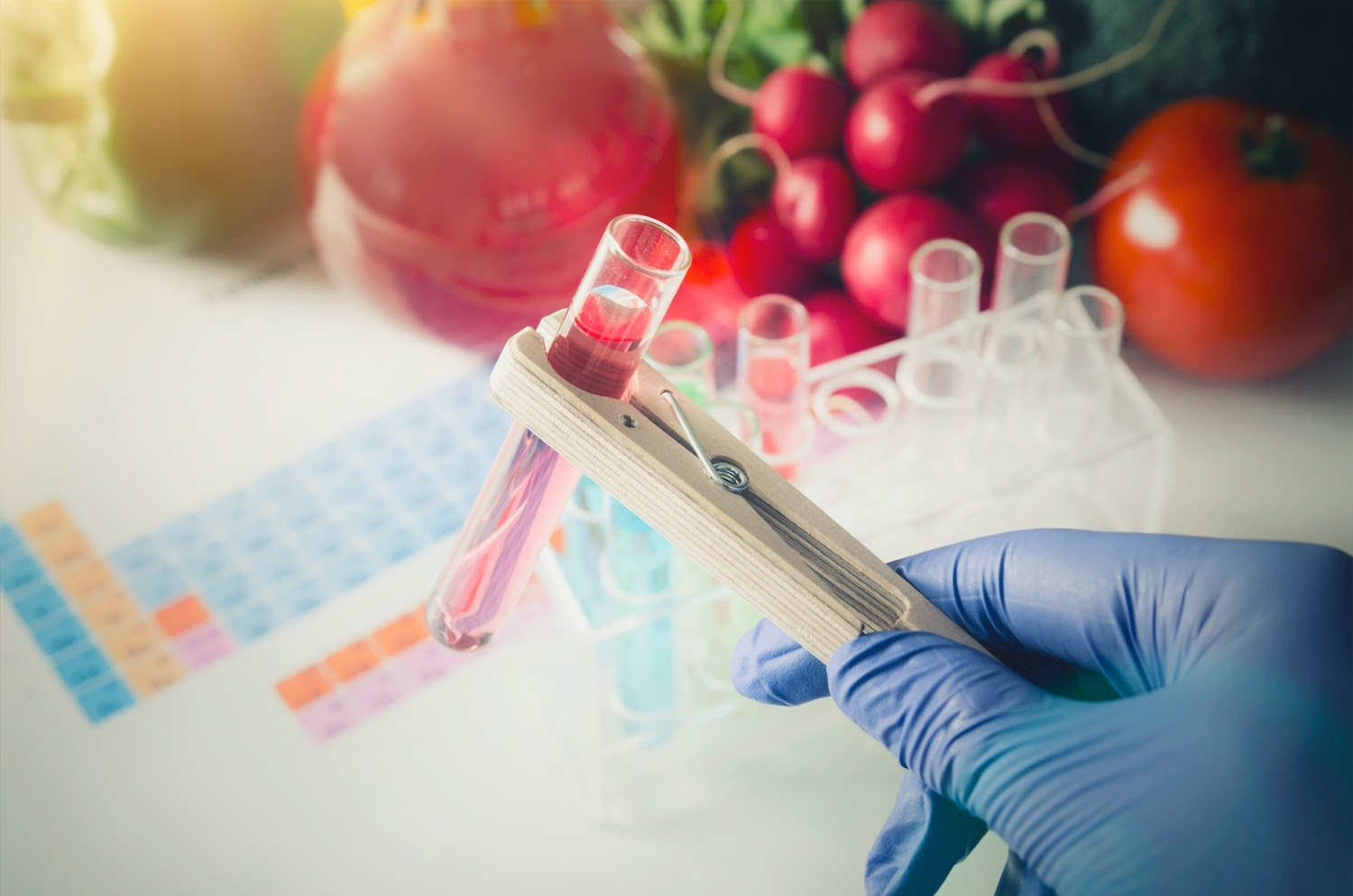 food allergy testing kit: Scientist holding a test tube in a clamp