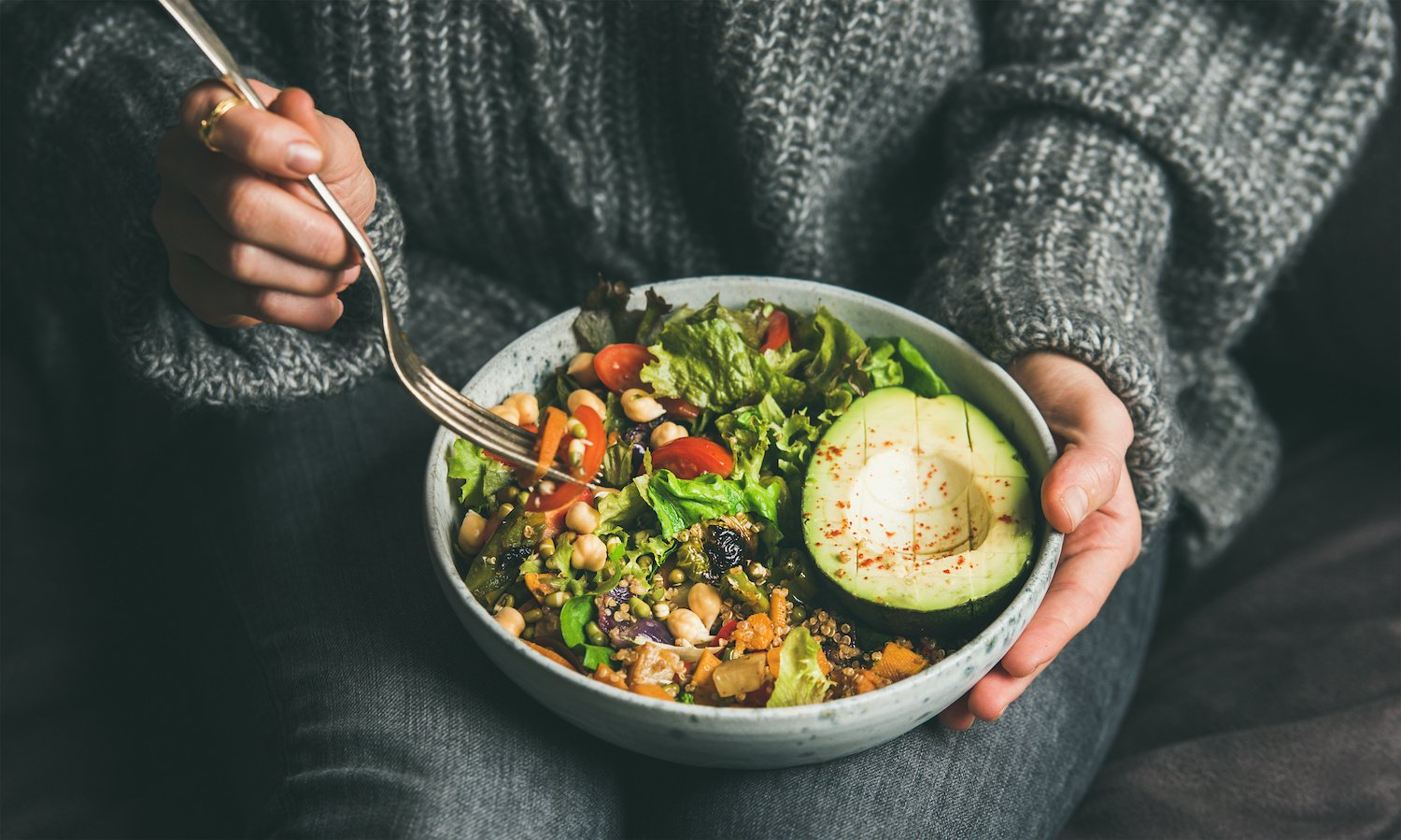 Woman holding a fork and a bowl of healthy food on her lap