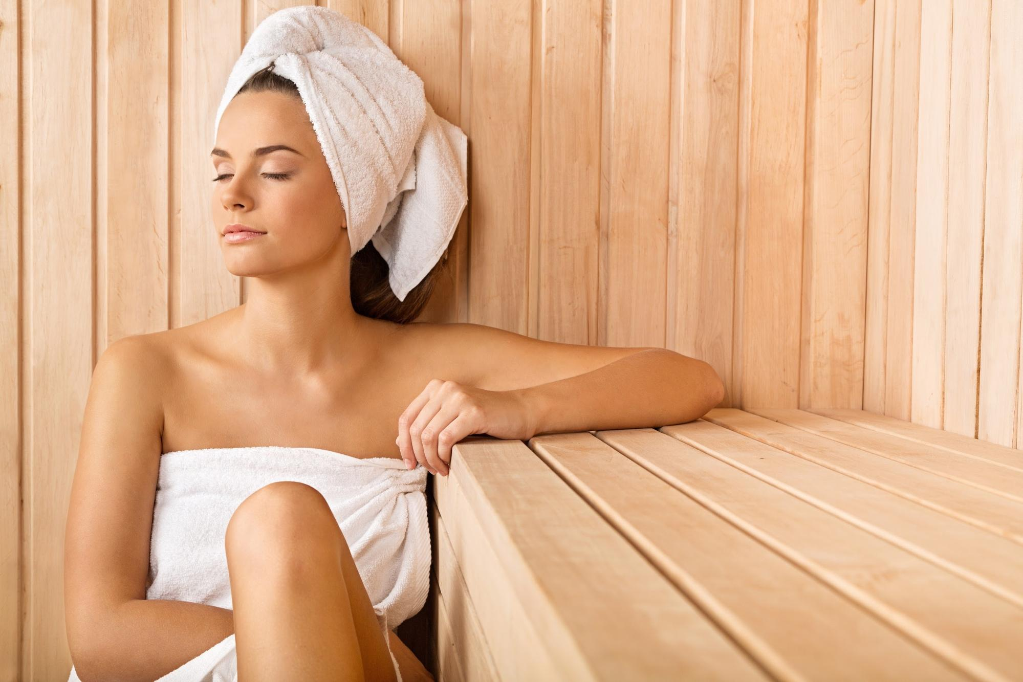 infrared sauna: Woman with a towel wrapped around her body and head in a sauna