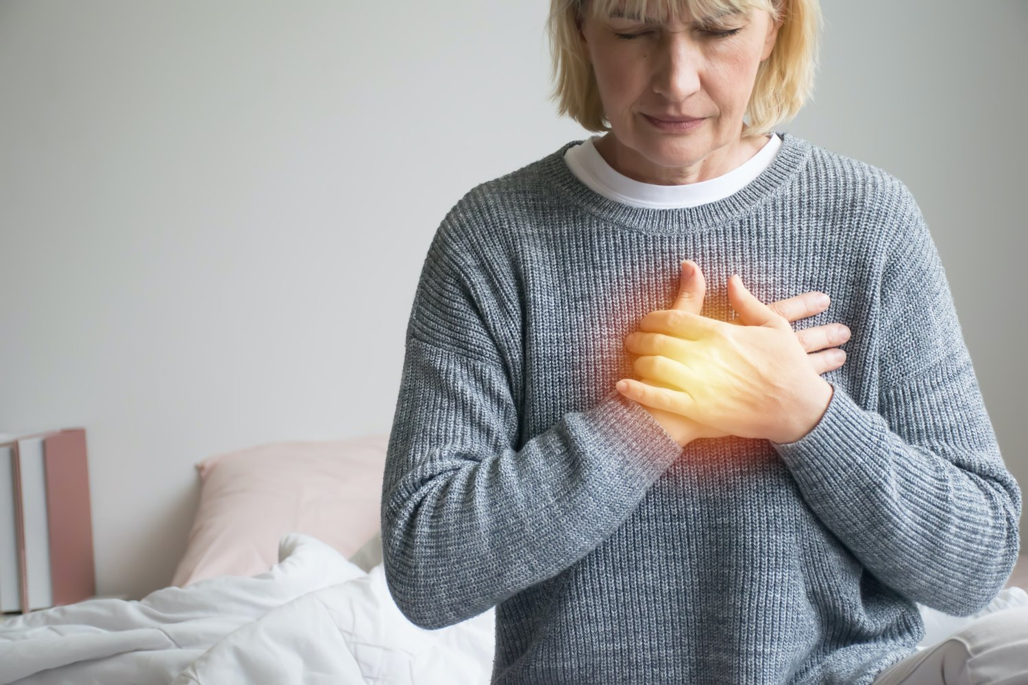 silent reflux: Woman holding her chest with her two hands