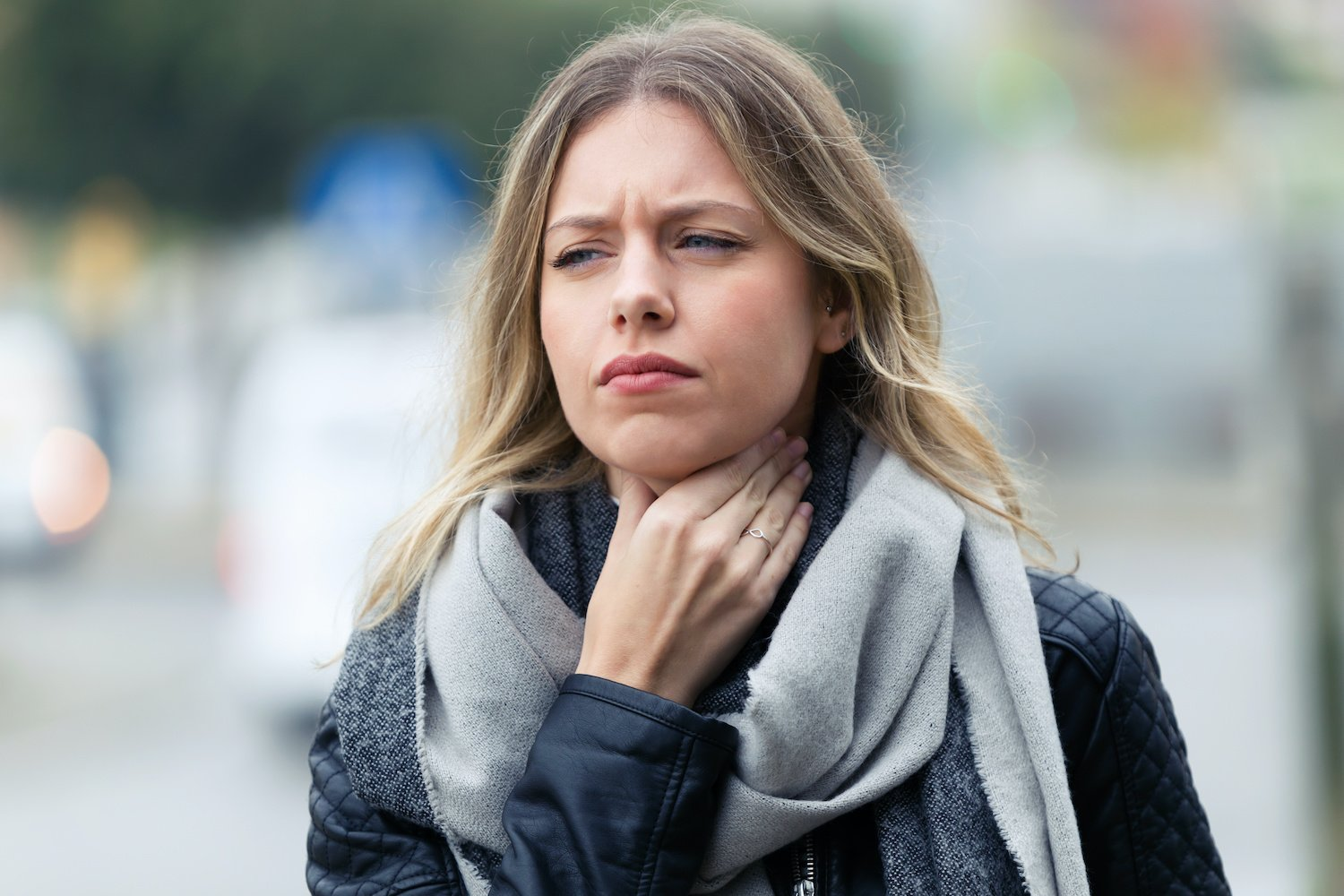 silent reflux: Woman in pain, holding up a hand to her throat