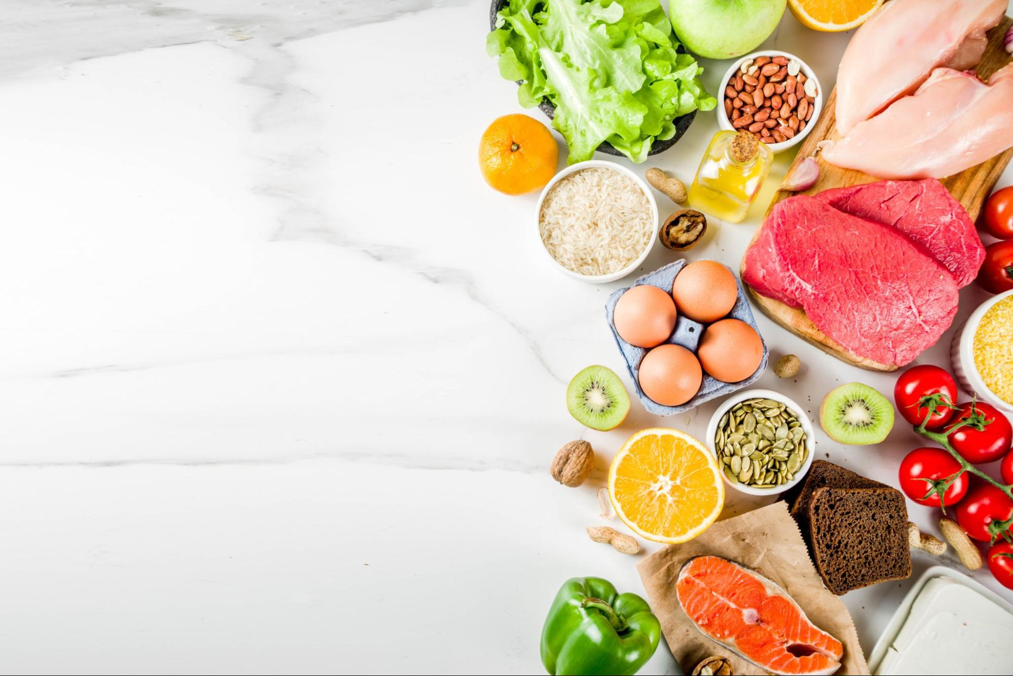 Variety of fresh fruits, vegetables, and meat on a white surface