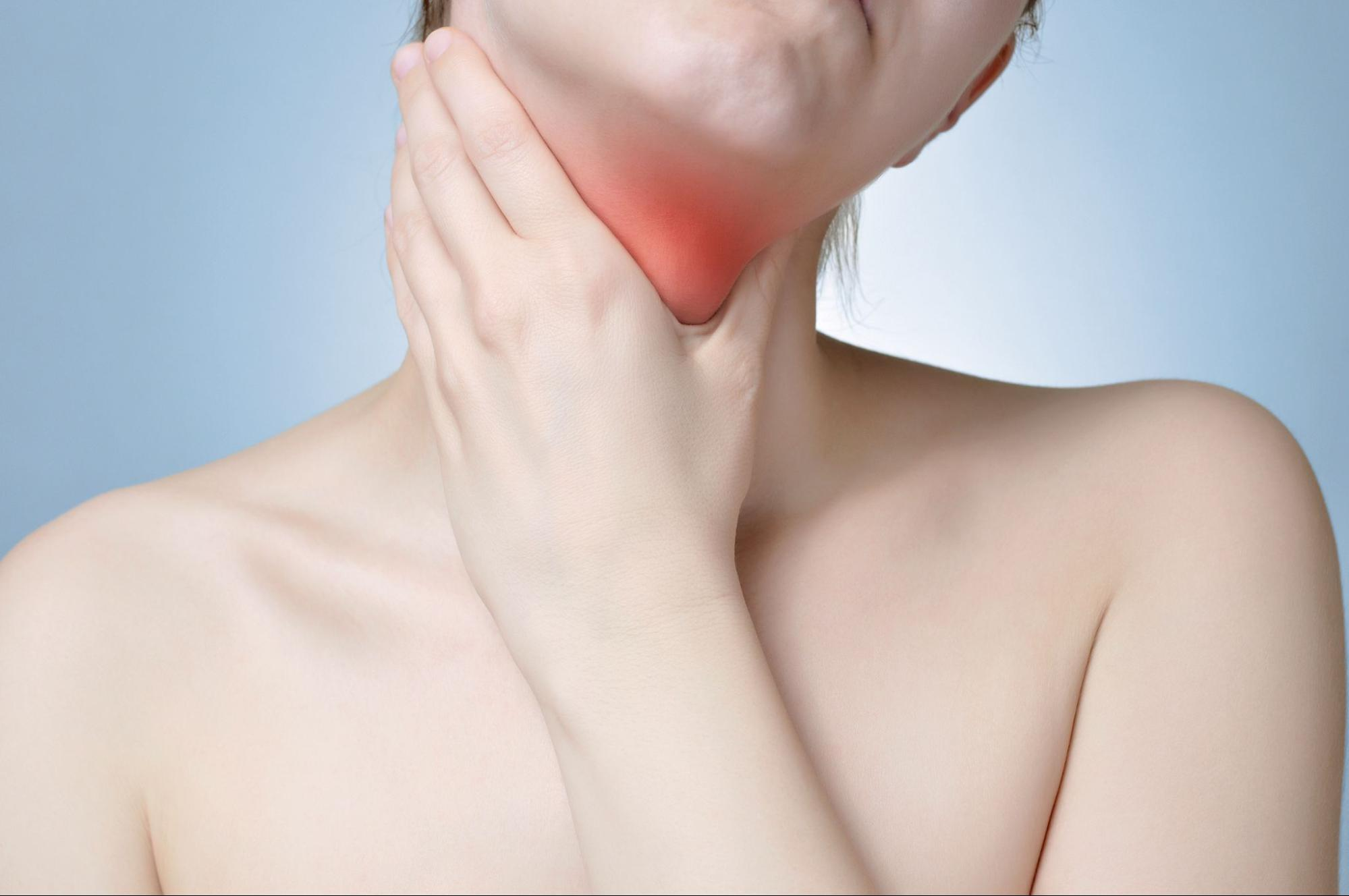 LPR diet: Woman in pain, holding up a hand to her neck
