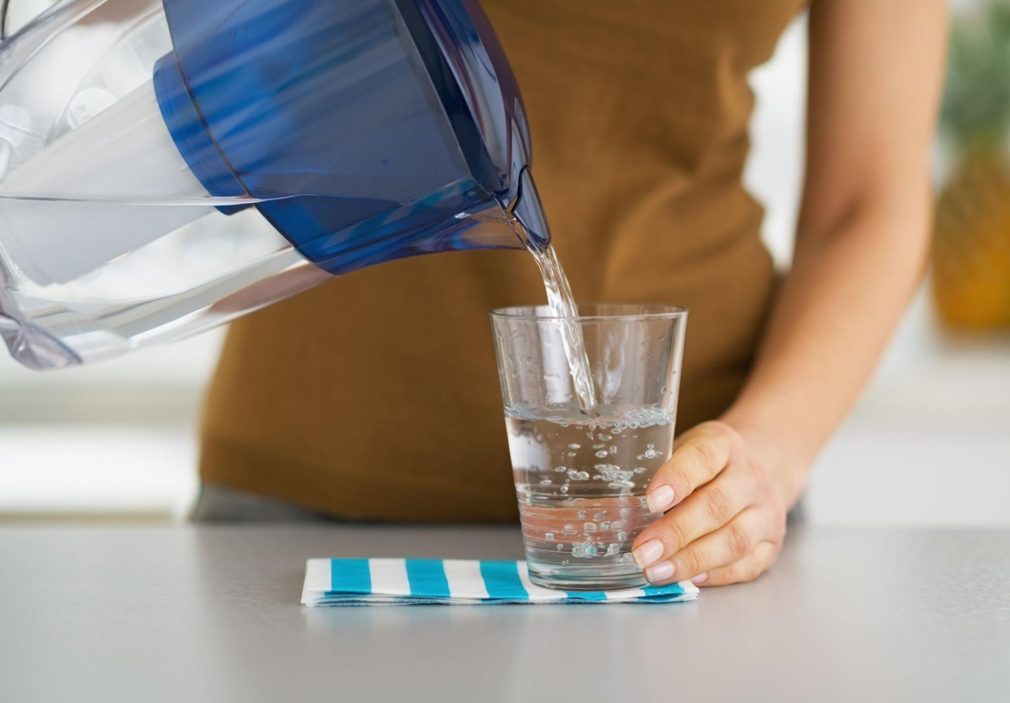 Close up shot of a woman pouring water in a glass