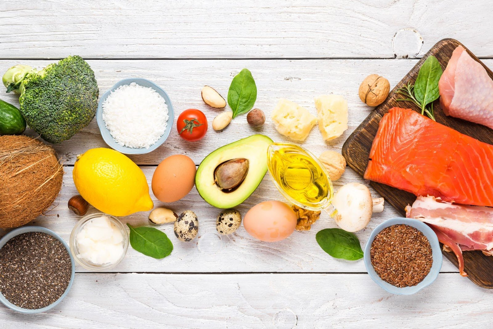 Variety of healthy foods on a white wooden surface