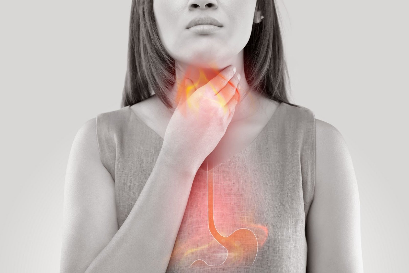laryngopharyngeal reflux: Woman touching her throat overlaid with an illustration depicting acid reflux