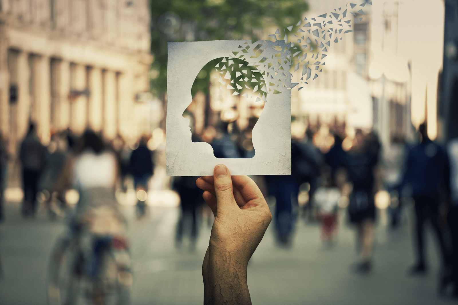 memory training: Person holding a paper cutout with the shape of a human head with pieces of it fading away