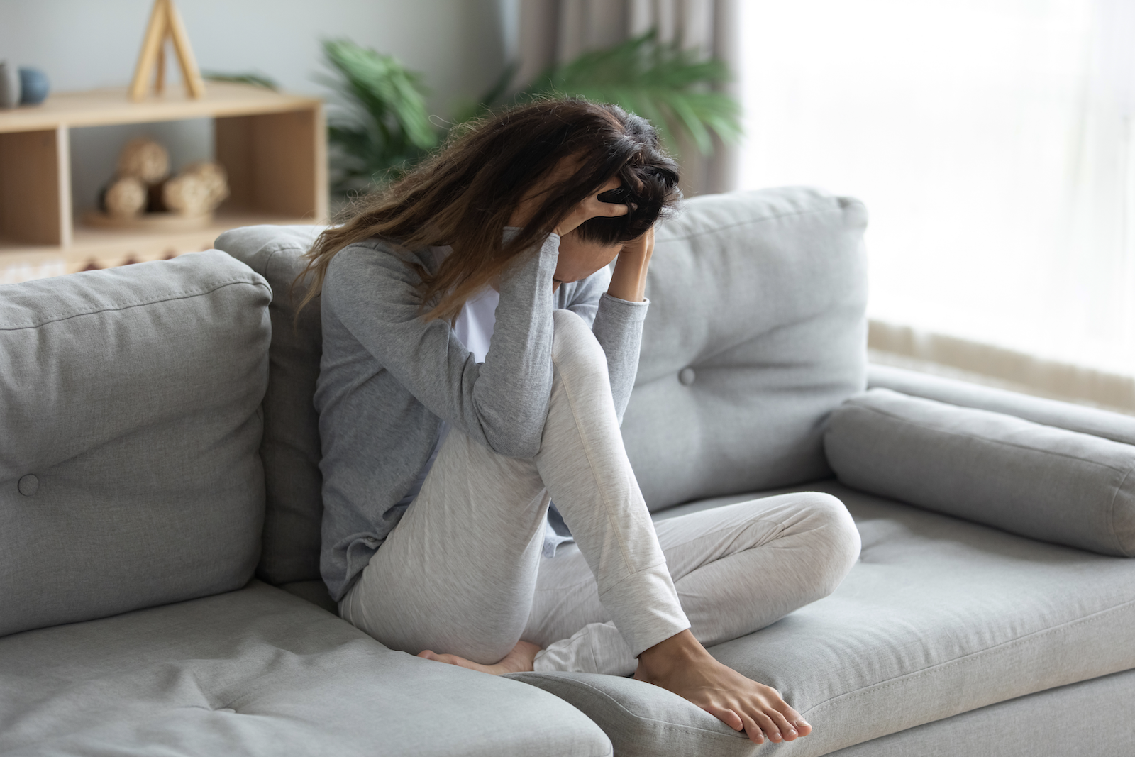 stressed woman holding her head while sitting on the couch