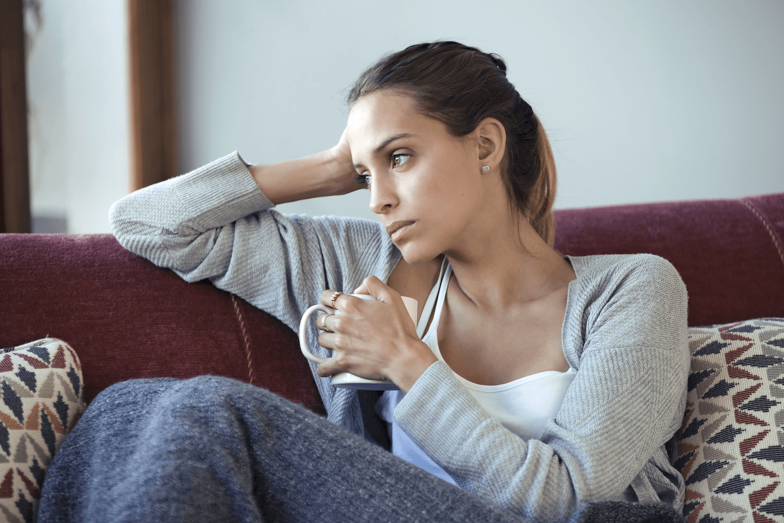 neuroplasticity healing: Woman looking deep in thought while sitting on a couch and holding a coffee mug