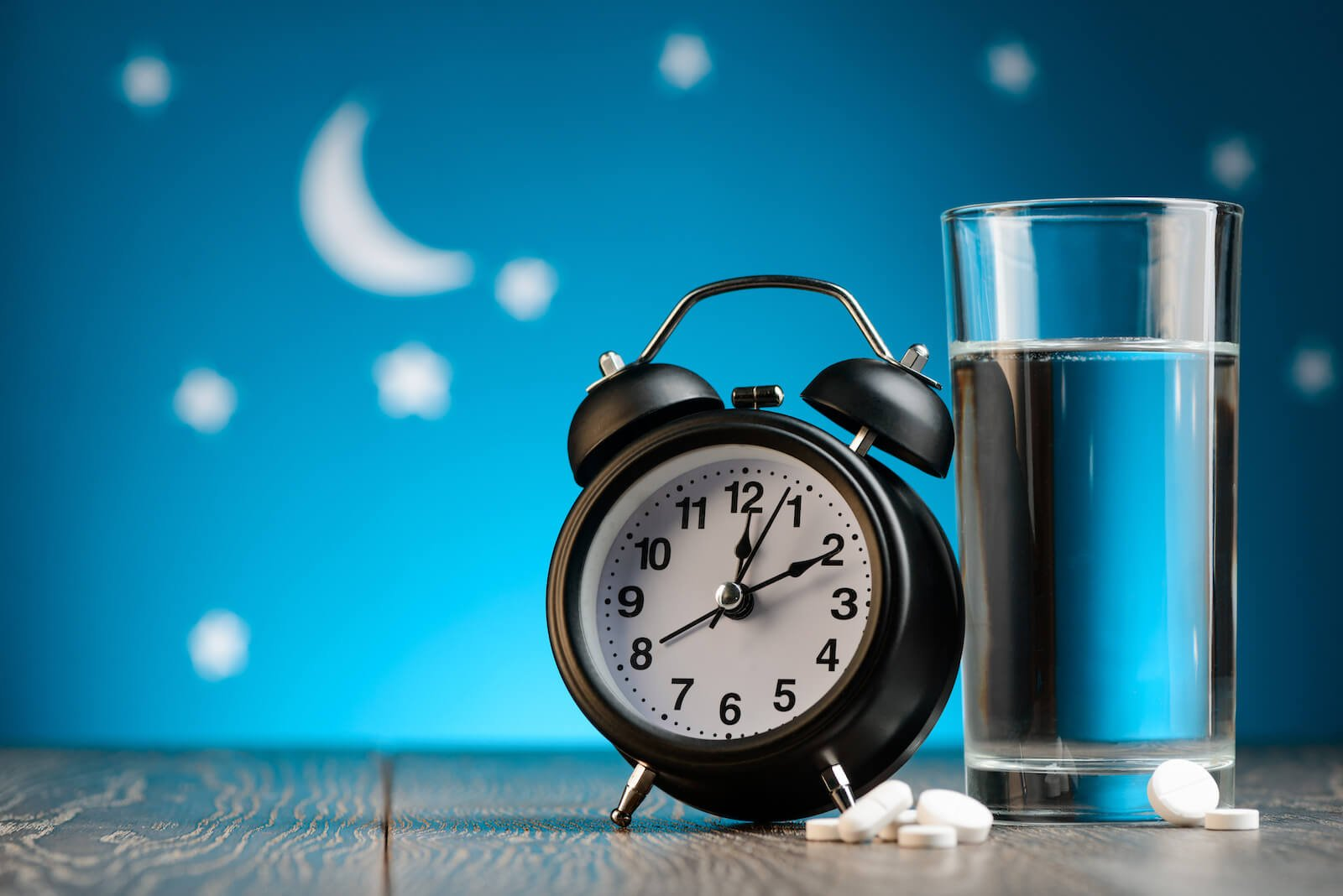 Alarm clock, pills and a glass of water