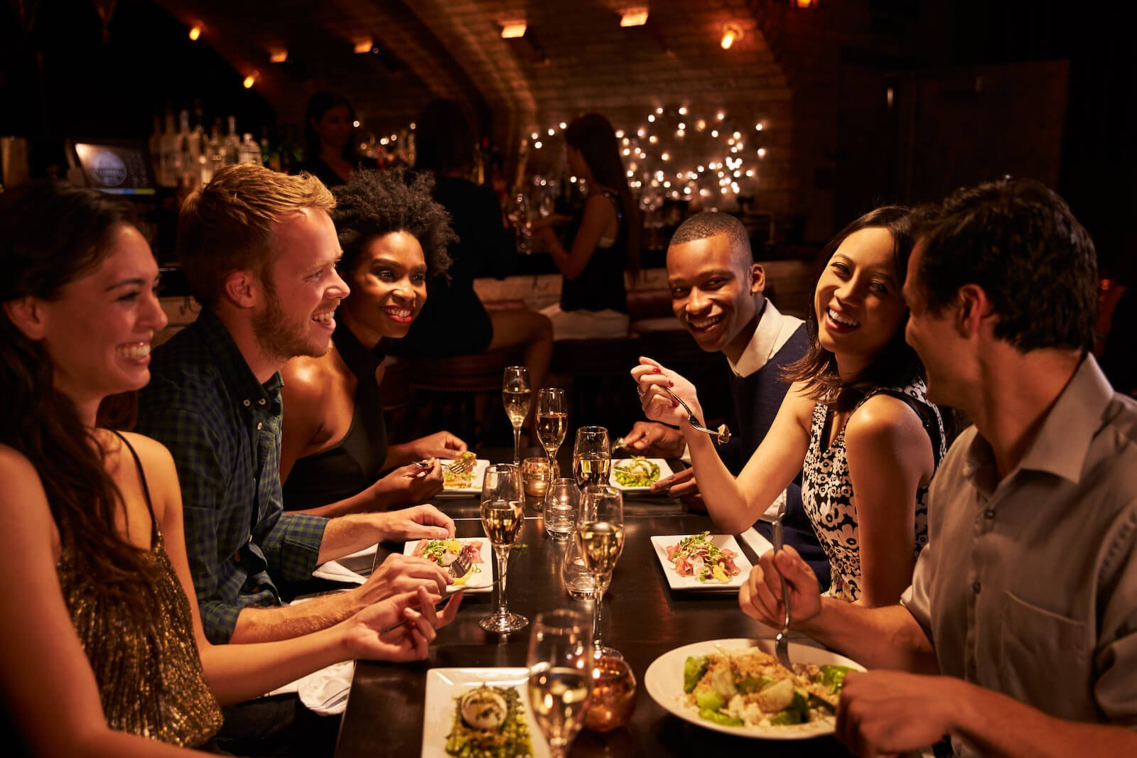 Elimination diet meal plan: group of friends having dinner at a restaurant