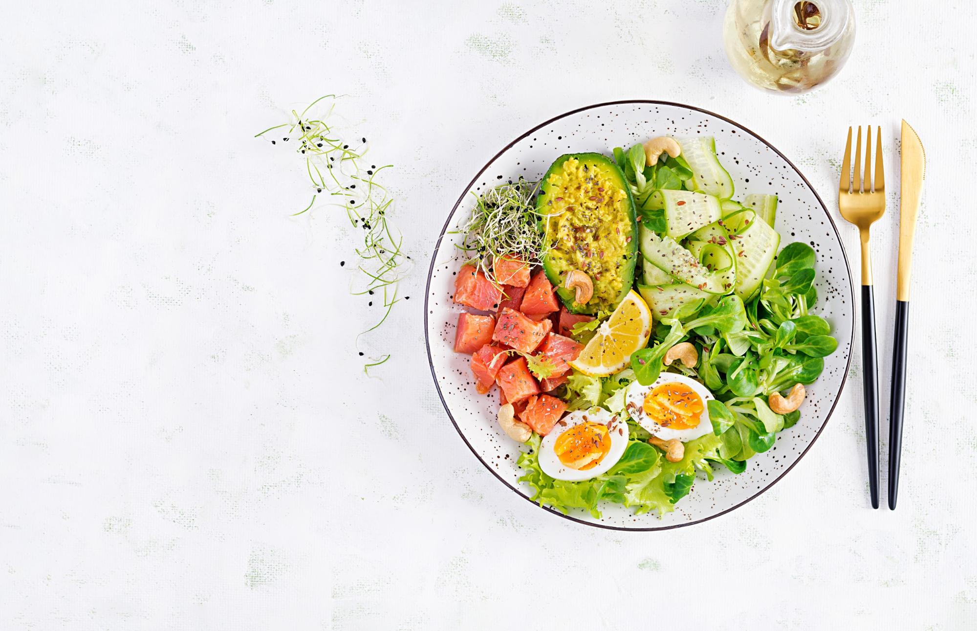 A plate of fruits, vegetables and eggs with gold knife and fork beside it on a white surface