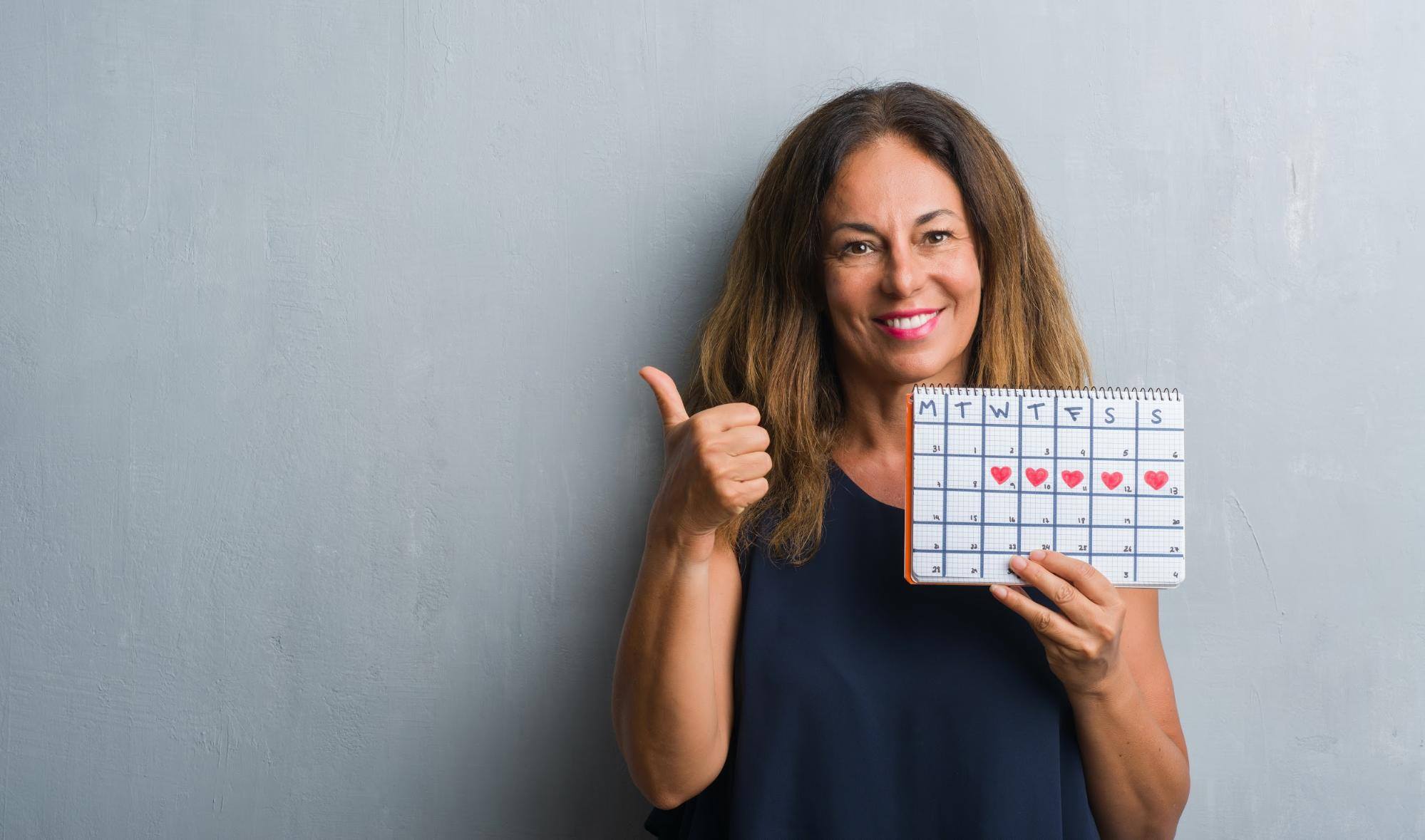 Smiling woman giving a thumbs up while holding her period calendar