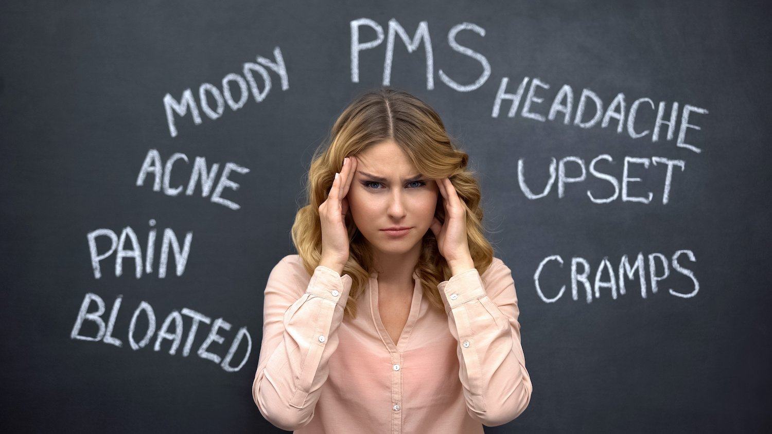 Woman holding her head in pain while symptoms of hormonal imbalance in women are written on a blackboard behind her