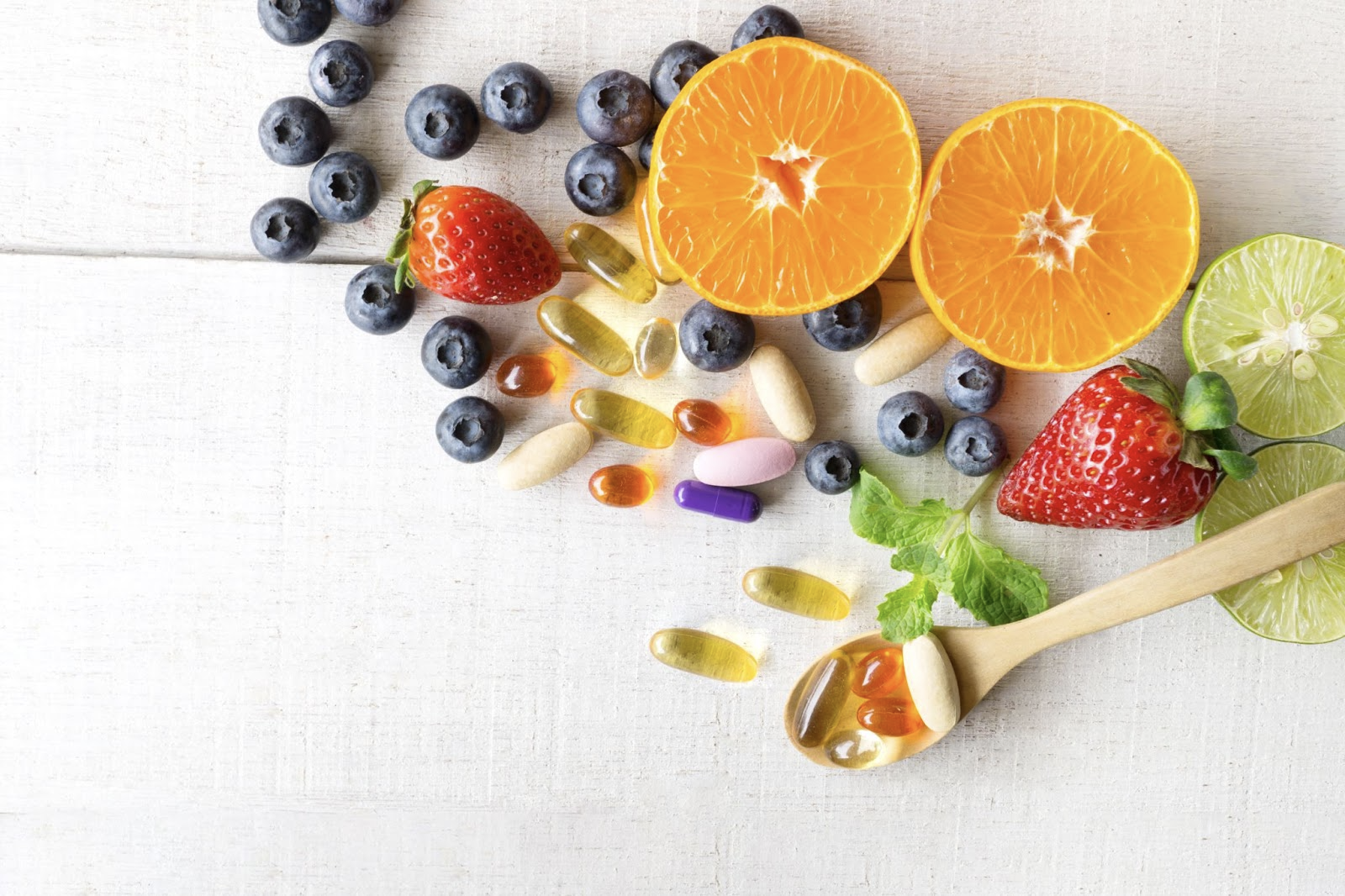 ulcerative colitis vs Crohns: Variety of fruits and capsules on a white wooden surface