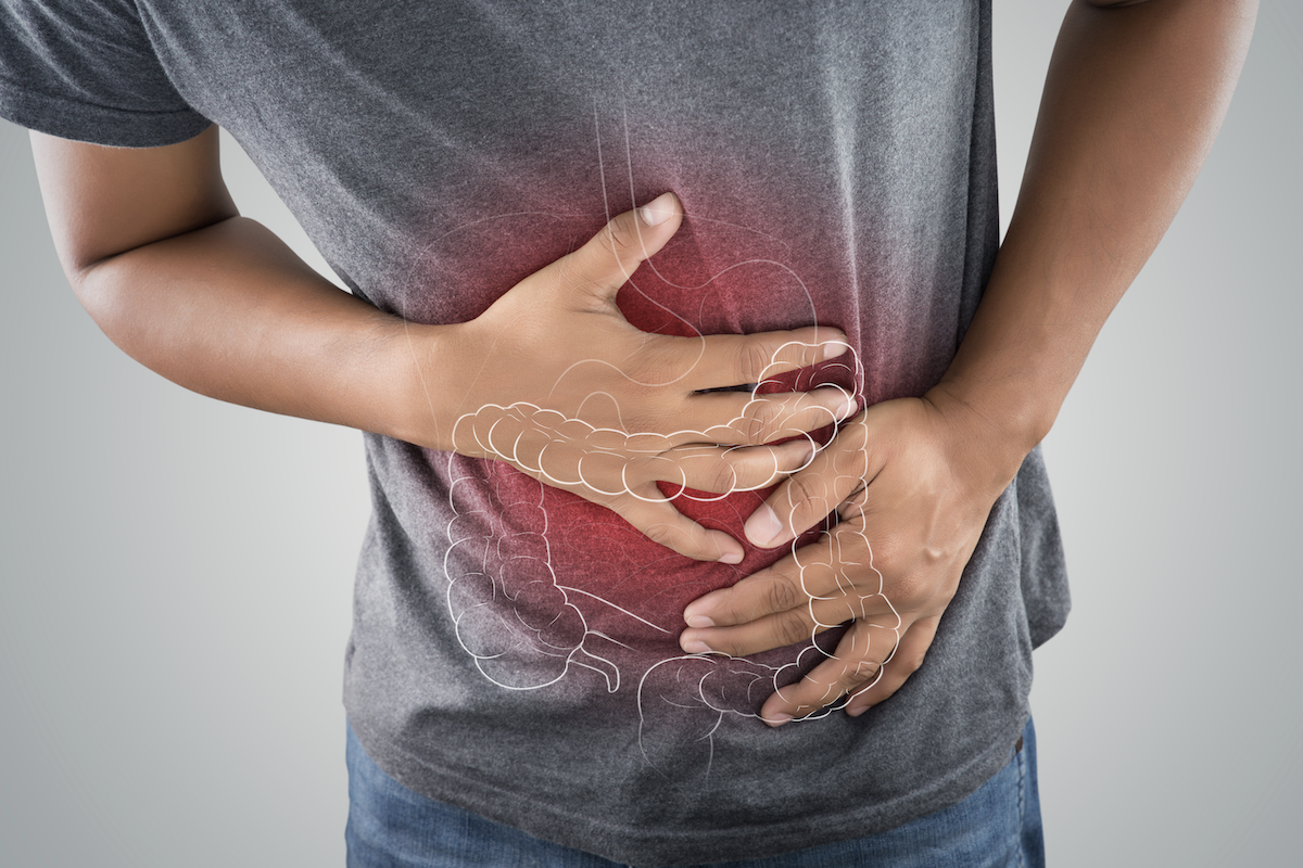 symptoms of colitis: Illustration of the large intestine against an image of a man with a stomachache