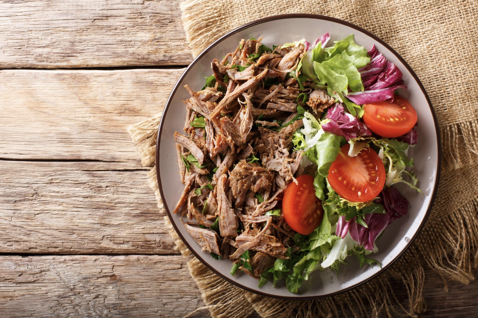ulcerative colitis vs Crohns: Bowl of salad with meat on top of a wooden surface