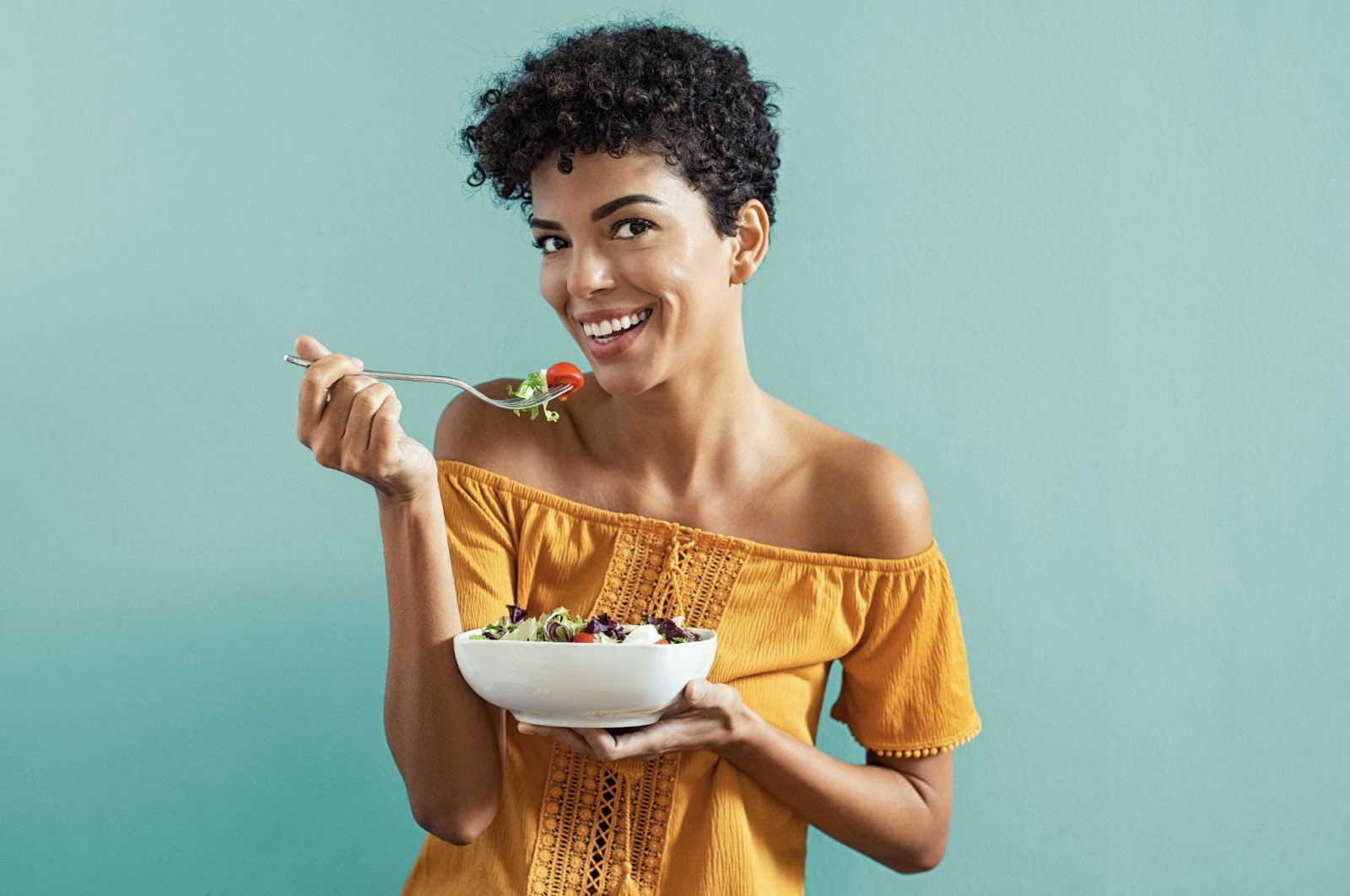 ulcerative colitis vs Crohns: Smiling woman eating a salad against a green background