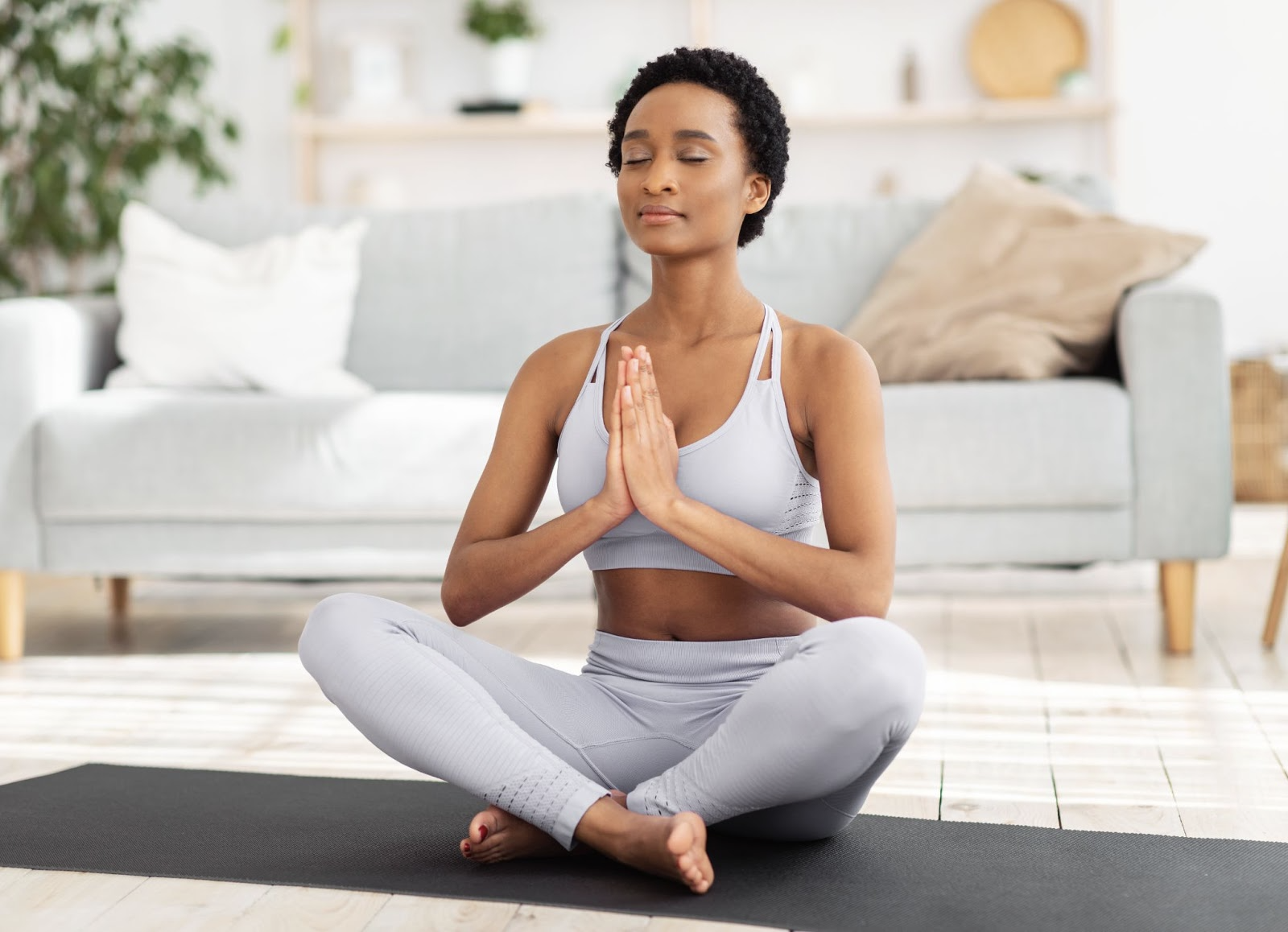 Woman meditating in her living room