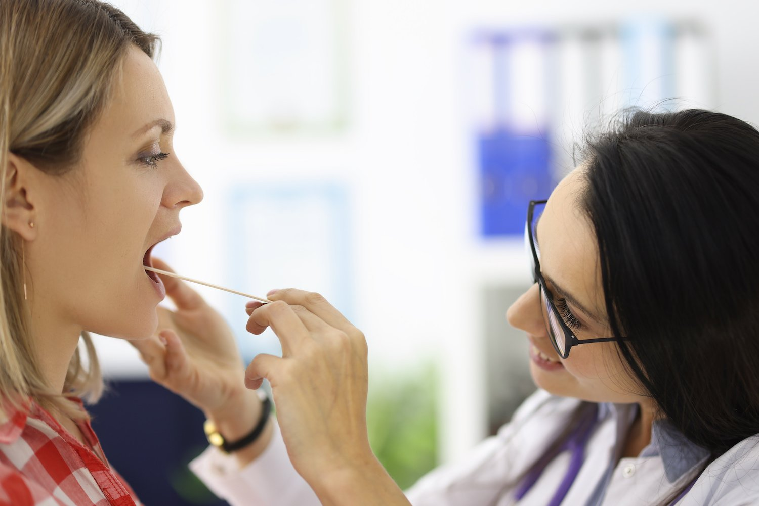 LPR treatment: Doctor checking a patient's throat using a wooden spatula